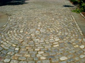 Driveway cobblestones in a circular pattern.