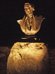 Outdoor accent lighting shines on a historical sculpture.