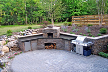 A patio with an outdoor kitchen island and a pizza oven