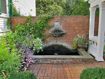 Brick Patio Wall Designs circular brick patio stands over pebble bed with brick wall surrounding elevated patterned space Brick Design With Wall Fountain