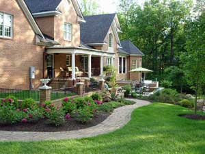 a pathway made from tumbled pavers curves around the side to the rear patio the backyard patio is terraced it is two levels with steps leading to the