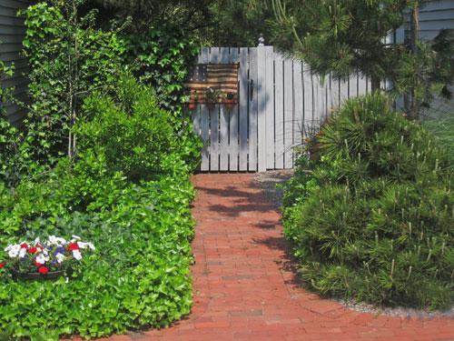 Brick walk leads to backyard gate.